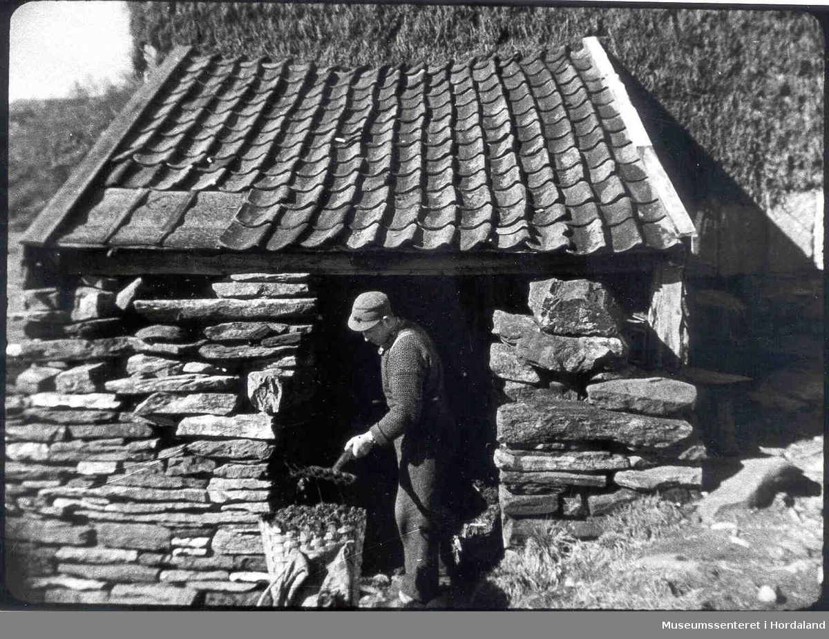 Havrå.Mann med møkkagreip. Mottinghus i stein. Flor med brakekledning i bakgrunnen. Kipe. Takpanner.  (Foto/Photo)