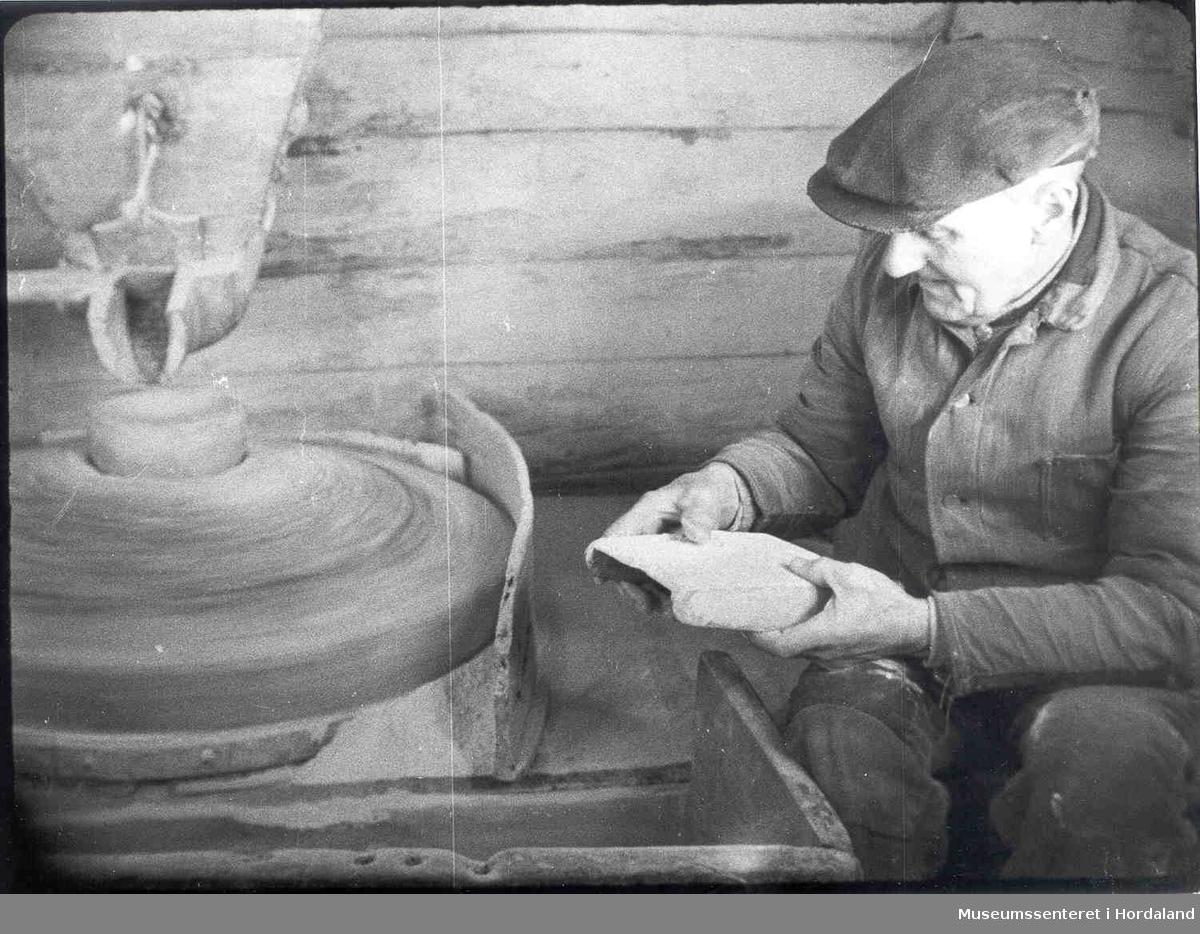 Havrå.Mann i kvernhus på Havrå. Kvern. Oppåsteinen og understeinen og skod`n, og litt av mjølskuffa. Grov tømmervegg. (Foto/Photo)