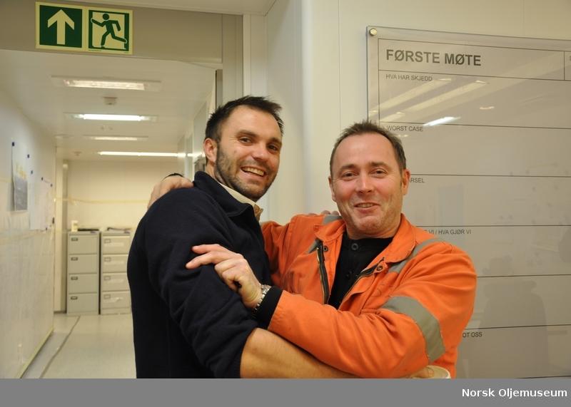 11b679a5 En mann i kjeledress løfter noen vekter til ære for fotografen under ...