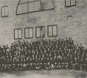 Gruppbild över hela personalen, omkring 160 man, utanför Nya hyttan, troligen 1915.