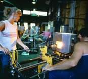 Glasblåsning vid Orrefors Glasbruk. Ett vinglas värms vid invärmningsugnen för påklippning av ben eller fot.