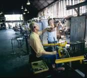 Glasblåsning vid Orrefors Glasbruk. Påklippning av fot till ett vinglas.