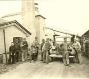 Disponent Oskar Jonsson och ett antal arbetare framför Kalksandstegelfabriken