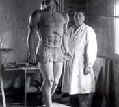"""Konstnären och skulptören Otto Jansson, Mörtfors med skulpturen """"Tarzan"""". Modell till skulpturen var Hardy Ahrland, Stockholm.  Bilden tagen i möbelfabrikens lokaler.  """"Tarzan"""" blev under årens lopp hårt tärd av väder och vind och förlorade även ett ben. Sterbhuset sålde skulpturen sommaren 1985 till filmaren och regissören Jan Troell för enligt uppgift 1 000 kronor."""