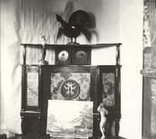 Detaljer i konstnären Otto Janssons hem i Mörtfors. Observera att papper uppsatts i rummets hörn för att framhäva skåpet. Väggen bakom papperet verkar att vara motivmålad. Dörrspeglarna målat på masonite. Medaljongen finns nu (1983) monterad på annan plats. Kvinnoskulpturen på golvet såld. I förgrunden en tavla med skärgårdsmotiv signerad av konstnären.