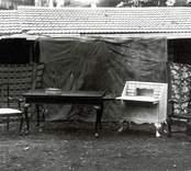 """Olika stilmöbler tillverkade vid Mörtfors Möbelfabrik före 1936 då fabriken och torkanläggningen nedbrann.  Fotograferingen är gjord framför torken som getts en """"lugnare"""" bakgrund genom upphängda tygstycken.  Bemärk att bordet har utdragsskivor, den vackra karmstolen samt det lilla syskrinet på bordet."""