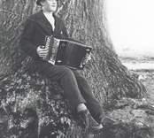 Helge Sandström med sitt dragspel fotograferad framför Emils ek på Ekudden.