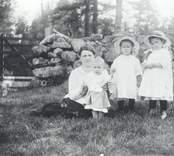 Bilden tagen innanför stenmuren vid grindstugan under Späckemåla i Misterhult socken. Linnéa Swahnberg med barnen Gunnar, Margit, Dagny.