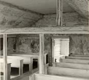 """Interiör mot dörren i Väderskärs kapell. Byggt 1590 och flyttat till platsen 1615.  """"Kapellet är ett lågt timmerhus med ett stort vapenhus med dörr i väster. Det är knuttumrat med inklädda knutar, klätt med stående panel troligen på 1700-talet. I inredningen, som är helt av trä, finns enkla rakryggade bänkar där det på flera platser finns inskurna bomärken. Altaret är ett enkelt, framtill klätt bord som även tjänar som predikstol. Väggar och tak är till största delen målade och målningarna är av två slag. En enklare typ av målning i allmogestil finns huvudsakligen i tak och gavlar. De framställer bla en Golgatascen, änglar, skepp mm och är daterade 1740. Övriga delar av kapellets innerväggar panelades förmodligen 1738 med redan förut målade brädor. Bland dessa kan bla urskiljas Kristi dop, Kristi uppståndelse mm. Numera utnyttjas kapellet till sommargudstjänster och bröllop bla. Genom länsstyrelsens beslut 1980 blev det ett byggnadsminne.""""  (hämtat från Nationalencyklopedin.)"""