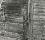 Närbild av en korsknutad, liggtimrad stuga i Högatorp.
