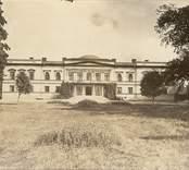 Gränsö slott,  gårdsfasaden. Byggt av timmer och klätt med  tjock puts. Byggt 1848 av byggmästare J. Jonsson, från Västervik  Den äldre byggnad som fanns ingick i den nya. - Huset vitt, ornament grå.
