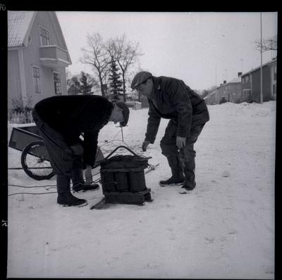 Två män vid en kylare.