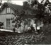 En familj avporträtterad utanför en stuga i Floda, Hjorted, 1919.