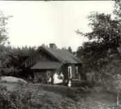 En familj dricke kaffe utanför sin stuga i Mossebo 1921.