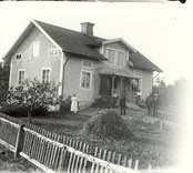 En familj utanför sitt hem i Långvik 1920.