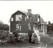 J Carlsson med familj utanför sitt hem i Åselid, Hjorted.