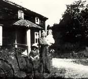 Två äldre kvinnor med ett barn utanför ett hus i  Hasselås