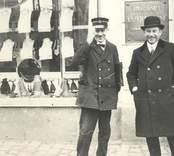 Exekutionsbetjänten, rådhusvaktmästaren Reuter (i uniformsmössa) utanför Ljungkvists tobaksaffär och herrekipering samt Smålands Enskilda Banks ingång.