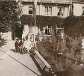 Kaffepaus i trädgården hos familjen Fogelmark. Här sitter Konsul Rob. Fogelmark, 1838-1909, fru Amelie Fogelmark, född Smith, 1846. Döttrarna Sigrid, 1868-1911, och Gunhild, 1879-1920.
