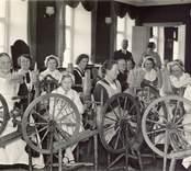 """Tjustbygdens kulturhistoriska förening.  """"Spånadstävlan l rådhussalen i Västervik år 1936. Deltagarinnaornas ålder varierar mellan 75 0ch 11 år och pris utdelades till  bland andra en sjuttioåring och en elvaåring. Många deltagarinnor äro iklädda den smakfulla Tjustdräkten.""""   I bakgrunden landshövding J.Falk."""