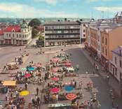 Vykort med motiv från Lilla torget i Oskarshamn, med pågående torghandel.