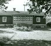 Manbyggnaden. Knuttimrad, klädd med panel av stående bräder med täcklister. Tak av 2-kupigt tegel. Rödfärgar med vita knutar, dörr- och fönsterfoder samt vitt takskägg och vita vindskivor. Glasverandan målad i vitt och brunt. Den övre bilden visar husets ursprungliga del, den undre även tillbyggnaden åt vänster.