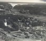 Flygfoto över Kristdala socken, Kristdala. Samhället med kyrkan, bostadshus och grusvägen.
