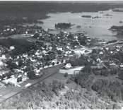 Flygfoto över Figeholm. Samhället med hus och grusvägen samt skog och Östersjön i bakgrunden.