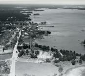 Flygfoto över Döderhult socken, Påskallavik. Samhället med kyrkan och bostadshus samt kalmarsund.