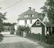 Bostadshus med garage, bakom ett staket vid en väg i Påryd. En bil står parkerad.