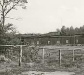 Motiv från Pukebergs glasbruk. En förfallen ekonomibyggnad och ett staket i förgrunden.