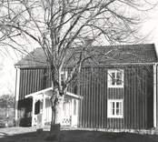Tvåvånings bostadshus med träfasad och farstukvist.