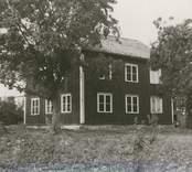 Timrad mangårdsbyggnad,, klädd med stående bräder med täcklister, tak av enkupigt tegel. Rödfärgad med vita hörn- och fönsterfoder.