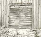 Detaljbild av dörr och fasad med stående panel.