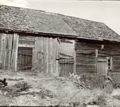 Gammalt stall med vertikala dubbelhaksknutar i timret. Sett från sydväst.