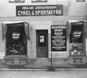 Helge Johansson Cykel och Sportaffär. Helge Johanssons Sportaffär låg vid östra sidan av stadshusplan, där senare kommunhuset Balder byggdes. Affären övertogs i mars 1935 av köpman Helge Johansson, som fram till 1960 under skicklig och framsynt ledning avsevärt utvidgade verksamheten. Firmans försäljning omfattade nu inte bara sportartiklar, utan även cyklar. mopeder och motorcyklar, såväl som radio och TV. En väsentlig gren av verksamheten var serviceverkstaden.för vilken Astor Magnusson var chef. Helge Johansson kom från Västsverige. Efter  hans död fortsattes firman av Astor Magnusson. Fastigheten revs  i januari 1980, men då hade Cykel och Sportaffären flyttat till Kalmar. (Källa : Gerhard Köppen)