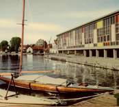 """Restaurang Slottsholmen är byggd i modernismisk stil som  karakteriseras av en avskalad och geometriskt enkel arkitektur då det är själva formerna och konstruktionen som står för det arkitektoniska värdet. """"Snabbseglare"""" i ek. Den 15 juni 1950 brann den """"gamla"""" restaurangen ned. Den 18 november påbörjades uppförandet av den nya restaurangen, som invigdes den 17 juli 1952. För publicering av bilden hänvisas till ägaren via Kalmar läns museum"""