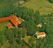 Flygfoto över Gunnabo. Gård med hagmark, ekonomibyggnader och ladugård.
