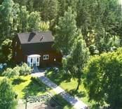 Flygfoto på ett enfamiljhus i Bäckebo. Trädgård och skogsmark.