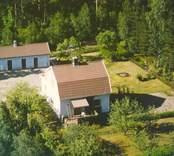 Flygfoto på ett enfamiljshus med sidobyggnad och trädgård samt skogsmark.