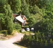 Flygfoto på ett enfamiljshus med sidobyggnad och skogsmark.