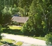 Flygfoto på ett enfamiljshus med trädgård och skogsmark.