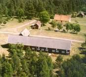 En gårdsmiljö i Luvehult, omgiven av skog.