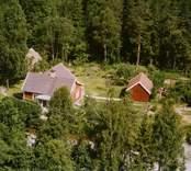 En tillbyggd stuga med uthus, på en skogstomt.