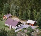 En skogstomt med villa, sidobyggnad och uthus, i Döderhult.