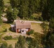 En skogstomt med ett tillbyggt enfamiljshus, i Döderhult.