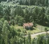 En skogstomt med ett enfamiljshus och uthus, i Döderhult.