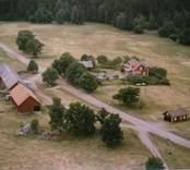 En gårdsmiljö, intill skogen, i Döderhult.