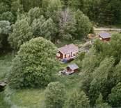 En stuga med uthus och trädgård, invid en sjö.