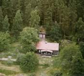 En skogstomt med ett fritidshus, och uthus, i Döderhult.